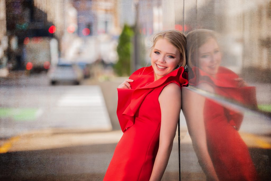 a senior leans on a wall for her senior photography in chattanooga